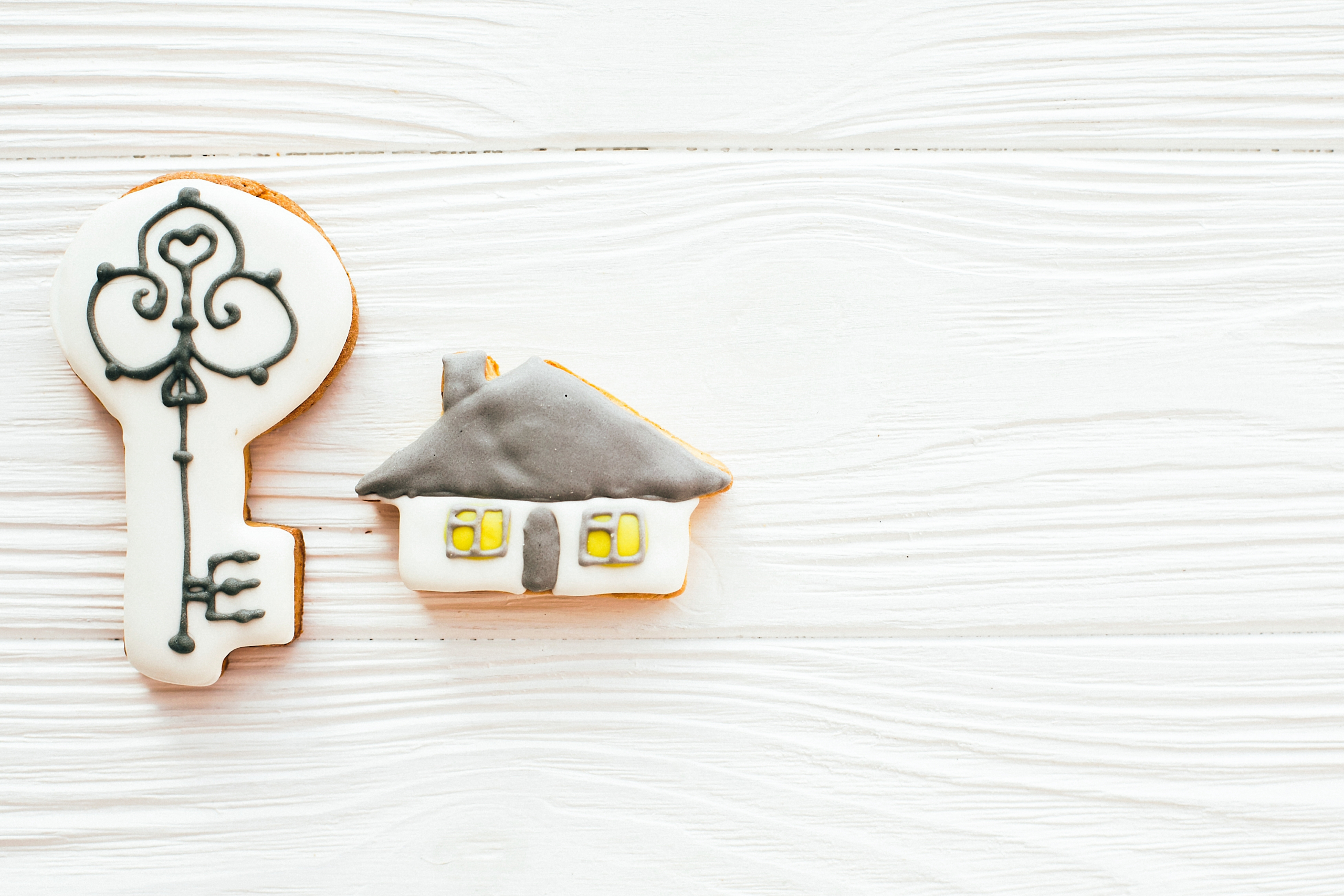 Key, house, welcome sign cookies on white wood, flat lay with space for text. Dream home concept. Home Sweet Home. Moving in new house, Welcome home set.